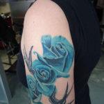 tattoo van drie realistische blauwe rozen en twee old school zwaluwen erbij