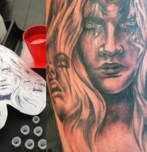fictie tattoo van drie vrouwen gezichten waarvan er eentje huilt