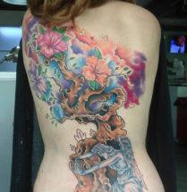 Tattoo met veel vrolijk kleurgebruik en een blauwe engel en een aziatische boom geplaatst op de rug.