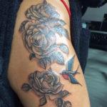 Old school tatoeage van ene zwaluw en enkele grijze rozen geplaatst op de schouder/bovenarm door Dutchink