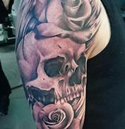 Realistische tattoo van rozen en een skull op bovenarm