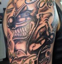 tatoeage lachen en huilen geplaatst op de schouder/bovenarm
