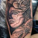 chicano tattoo van een vrouw met enkele kleine rozen geplaatst op de bovenarm bij Dutch Ink