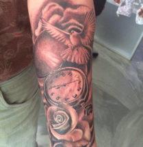 Mooie tattoo met veel verschillende illustraties bijvoorbeeld van een duif een zakklokje en een roos gezet door Dutchink