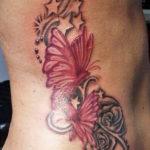 tattoo van twee rode clinders met een zwarte roos erbij gezet op de zij