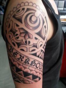 tribal tatoeage geplaatst op de bovenarm met een tekst erin
