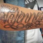 naam tatoeage van vajenne met een hartje en twee bloemen en een hoop sierlijke lijnen