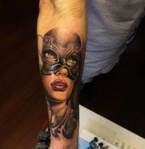 Tattoo op de onderarm, vrouw met masker op.
