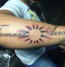 Namen tattoo met zon op onderarm