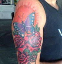 Vlinder en bloemen op bovenarm
