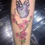 Vlinder met bloemen op onderbeen