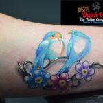Vogeltjes met bloemen op bovenarm