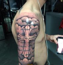 Kruis met tekst op bovenarm