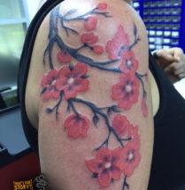 Boom tak met bloemen op bovenarm