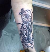 Dromenvanger met bloemen en een vlinder op onderarm