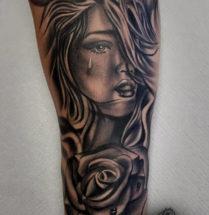 Vrouw met traan en bloem op onderarm