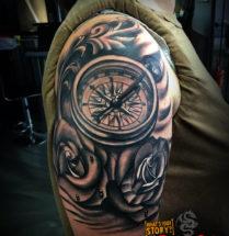 Kompas met bloemen op bovenarm