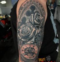 Bloemen en klok op bovenarm